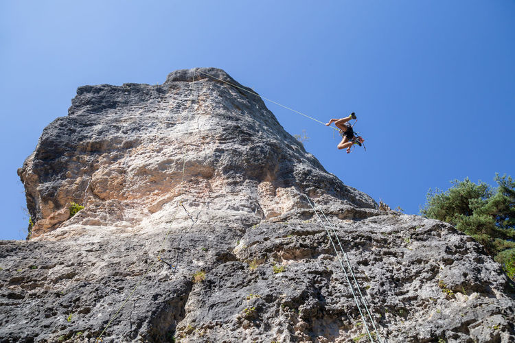 Low angle view of man rock climbing against clear blue sky