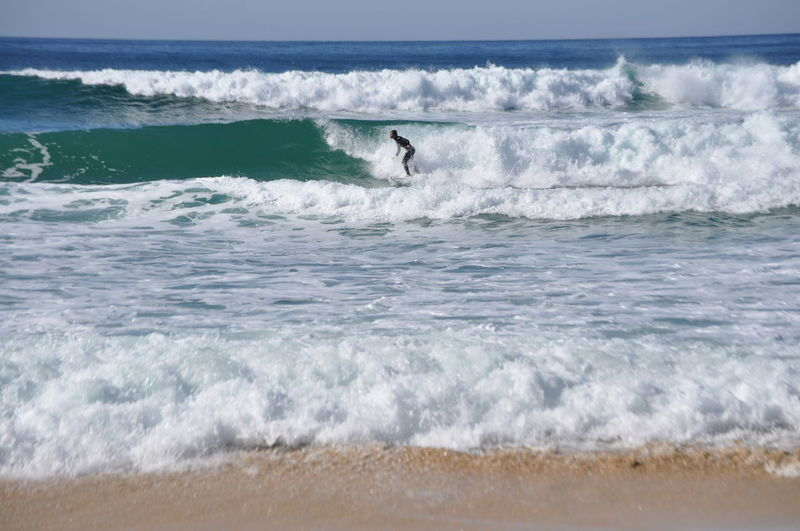 Side view of person surfing in sea