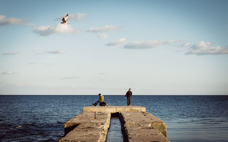 Man and woman on pier by sea against sky