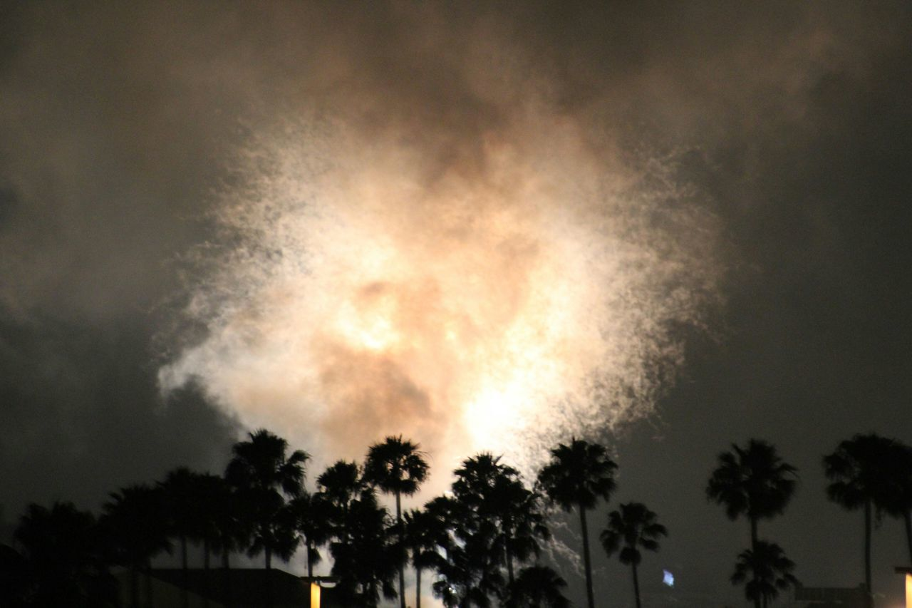 low angle view, silhouette, tree, sky, night, exploding, danger, motion, no people, firework display, outdoors, cloud - sky, palm tree, nature, scenics, beauty in nature, illuminated, building exterior, architecture