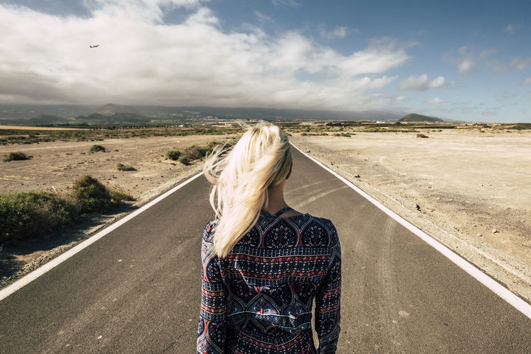travel and future choices concept with blonde young millennial girl viewed from rear walking on a straight long road - airplane fly in the background - people moving and enjoying the world concept Road Cloud - Sky Sky One Person Real People Lifestyles Landscape Environment Transportation Leisure Activity Hair Women Nature Standing Day Casual Clothing Land Rear View Adult Hairstyle Outdoors Wind Blond Hair Adventure Arid Climate