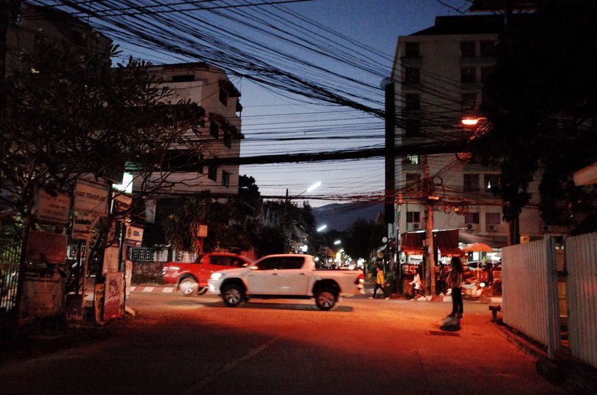 Built Structure Car Transportation Land Vehicle Building Exterior Architecture Street Mode Of Transport Road Cable Night Outdoors Electricity  Sky City Men Illuminated Electricity Pylon Real People Adult