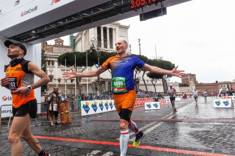 Rome, Italy - March 22, 2015: Some participants in the twenty-first Rome Marathon run through the last meters to the finish line. Arrival Athlete Atletic City Life Competition Day Finish Line  Happiness Happiness Italy Marathon Outdoors Rain Rome Runners Running Street Running Water