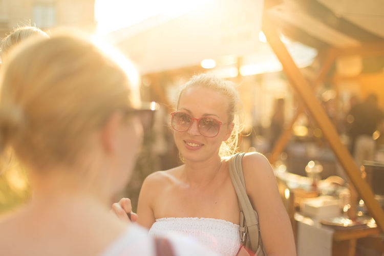 Smiling woman wearing sunglasses standing outdoors