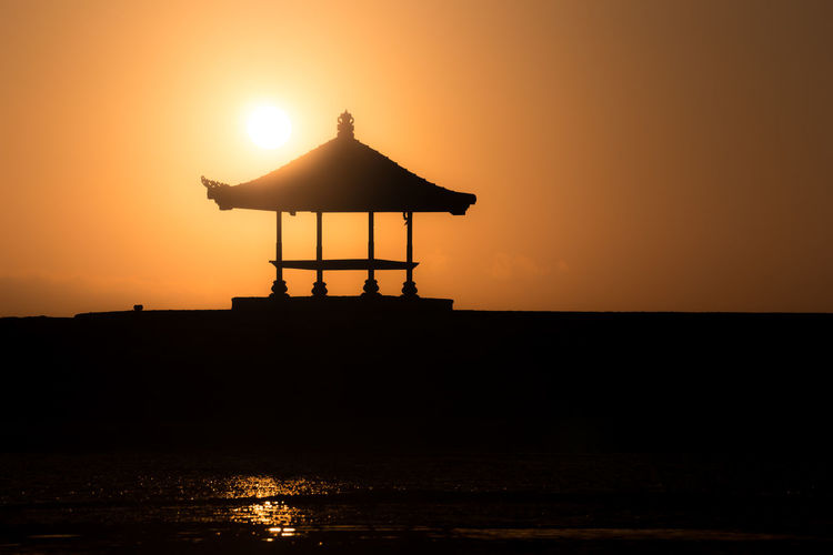 Cozy small traditional wooden house at Bali beach shot when sunset or sunrise. Enjoy fresh windy beach at small teak house in the morning or afternoon. Silhouette building with full round sun behind. Morning Afternoon Bali Beach Cloudy Cozy Dramatic Sky Enjoy Fresh Full House Red Relax Round Shade Shadow Silhouette Sky Sun Sunrise Sunset Tea Teak Traditional Windy Wooden Orange Color Water Beauty In Nature Scenics - Nature Tranquil Scene Nature Tranquility Built Structure Architecture Idyllic Non-urban Scene Sea Clear Sky No People Outdoors Horizon Over Water Silhouette Motivation Romance Of Nature Calmness Silence Silence Of Nature