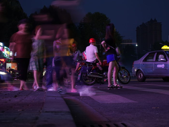 People riding motorcycle on road at night