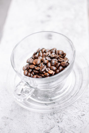 Food And Drink Food Indoors  Freshness Glass - Material Close-up Roasted Coffee Bean Brown Large Group Of Objects High Angle View No People Still Life Focus On Foreground Coffee Glass Container Coffee - Drink Drinking Glass Table Raw Food Crockery