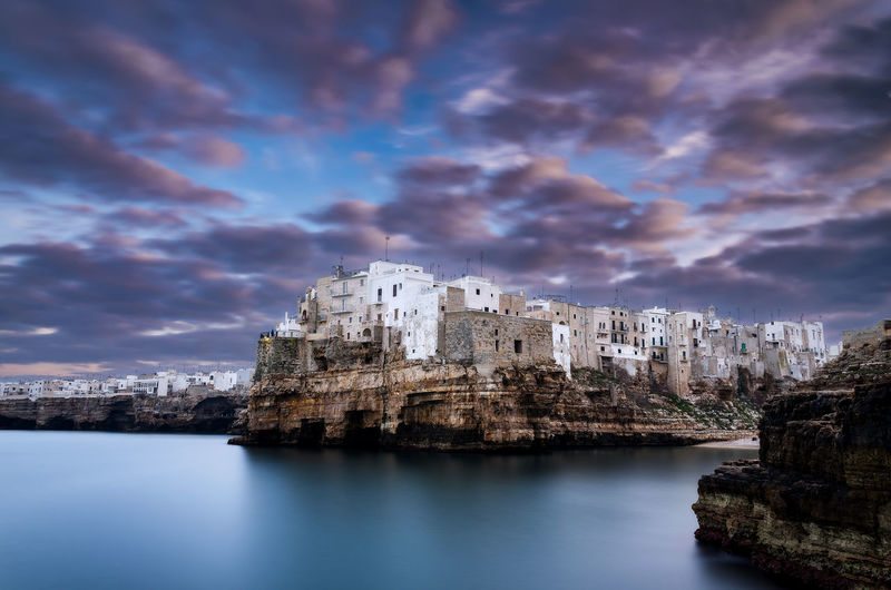 Buildings by sea against cloudy sky at dusk