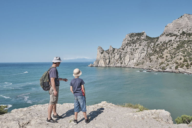 A boy and his grandfather standing on the shore of the bay and looking at the rock.