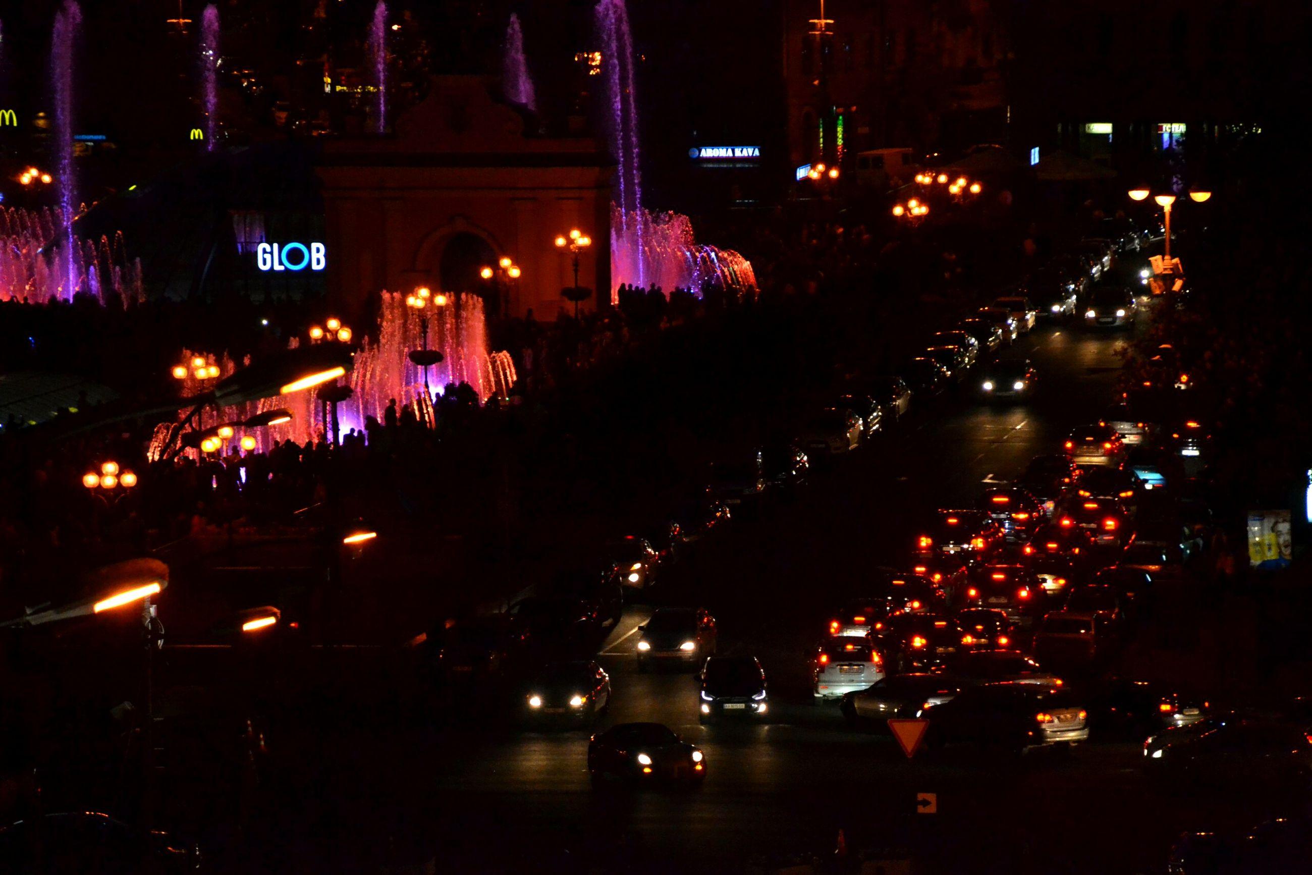 illuminated, night, land vehicle, car, city, large group of people, outdoors, architecture, people