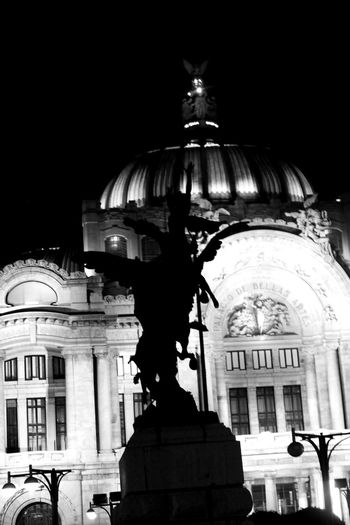 Low angle view of statue against illuminated building