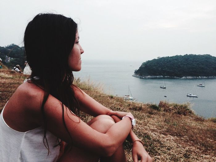 Beautiful Woman Sitting On Cliff By Sea Against Sky