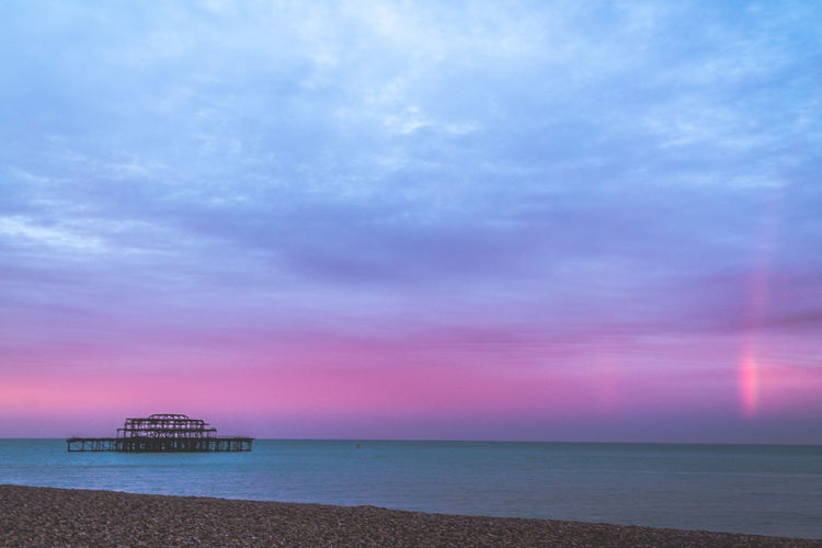 Dawn on the Beach - Brighton. Abandoned Buildings Abandoned Places Beauty In Nature Blue Water Brighton Calm Dawn Double Rainbow Horizon Over Water Nature Ocean Outdoors Rainbow Ruins Scenics Sea Seascape Sky Sunrise Tranquil Scene Tranquility Travel Photography Neon Life Visual Creativity British Culture The Minimalist - 2019 EyeEm Awards