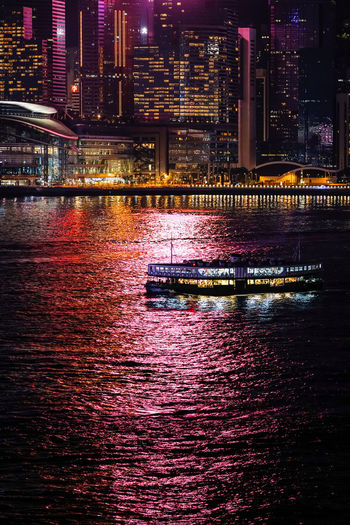 Illuminated modern buildings by river at night