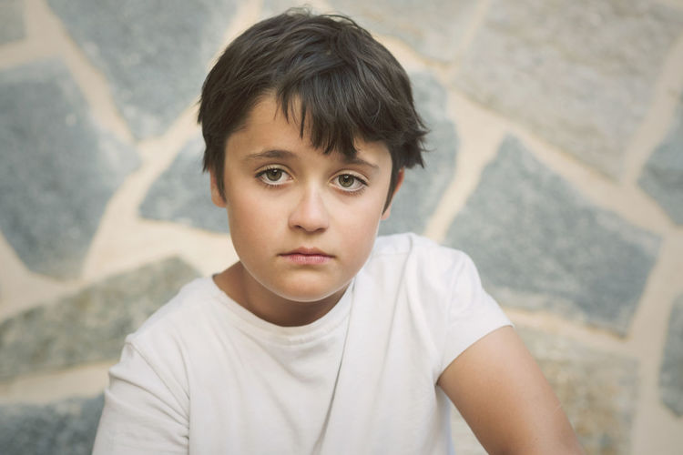 Close-up portrait of boy sitting against wall