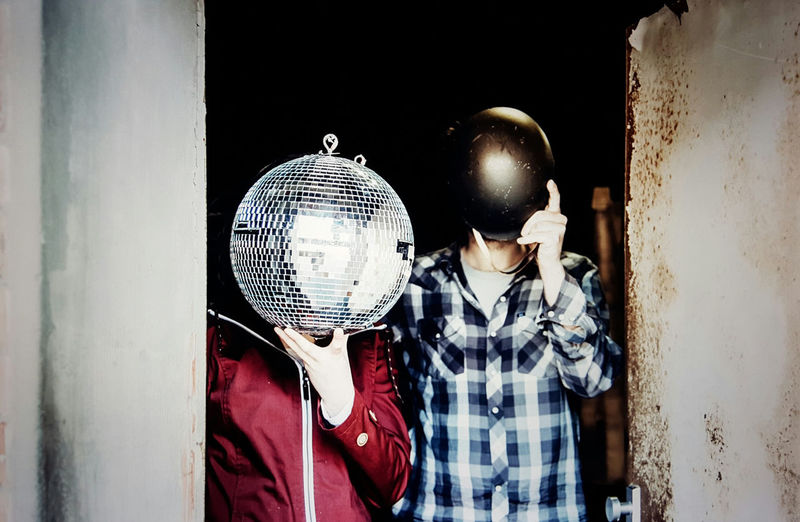 couple shot in Hamburg Absurd Ballhead Blind Can't See Couple Disco Ball Doorway Funny HEAD Head Replaced Head Replaced By Object Helmet Man And Woman No Head People Red And Blue Two People Young People Hipster