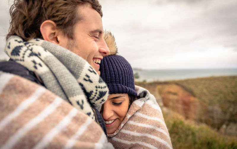 Closeup of young happy couple laughing under blanket in a cold day with sea and dark cloudy sky on the background Outdoors Nature Horizontal Woman Man Two People Love Romance Winter Cold Temperature Female Male Romantic Autumn Fall Hat Scarf Clouds Meadow Togheter Boyfriend Girlfriend Blanket Happiness Embracing