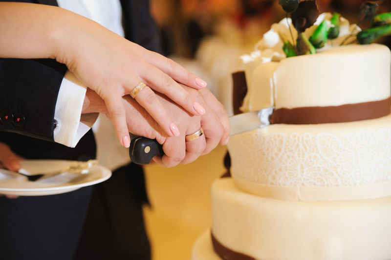 Cropped Image Of Bride And Groom Cutting Wedding Cake