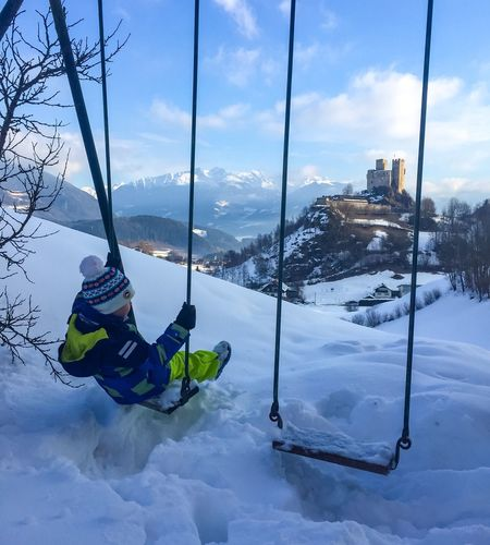 High angle view of boy sitting on swing over snow covered landscape