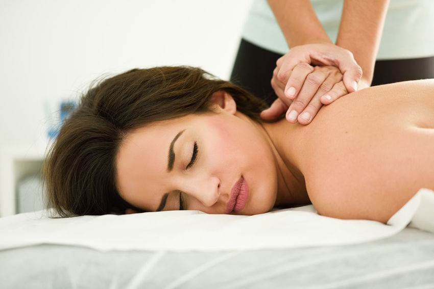 Young woman receiving a back massage in a spa center. Female patient is receiving treatment by professional therapist. Back Physio Woman Beauty Female Girl Massage Massage Therapy Physiotherapy Spa Young Adult Young Woman Young Women