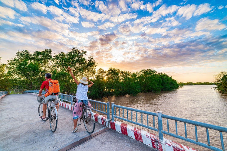 People riding bicycle by water against sky