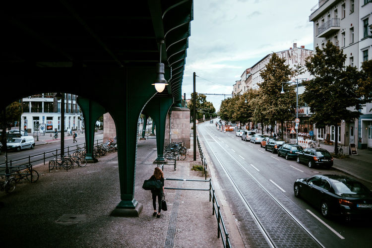 High Angle View Of Woman Walking On Sidewalk By Bridge In City
