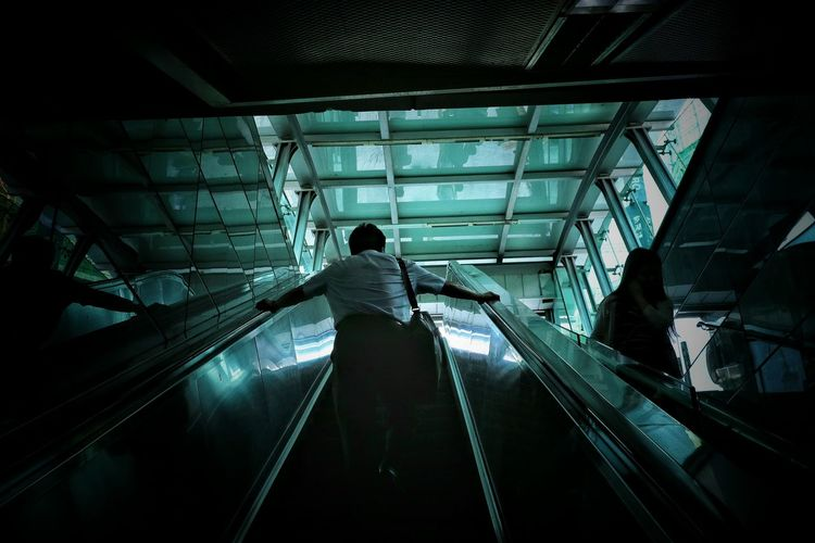 Low Angle View Of Man On Escalator