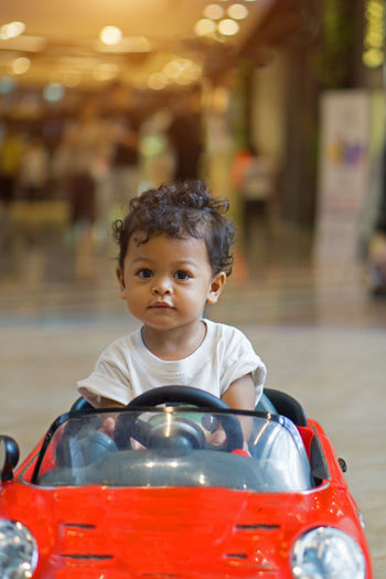 Close-up portrait of cute boy riding toy car
