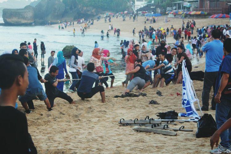 People playing tug-of-war at beach