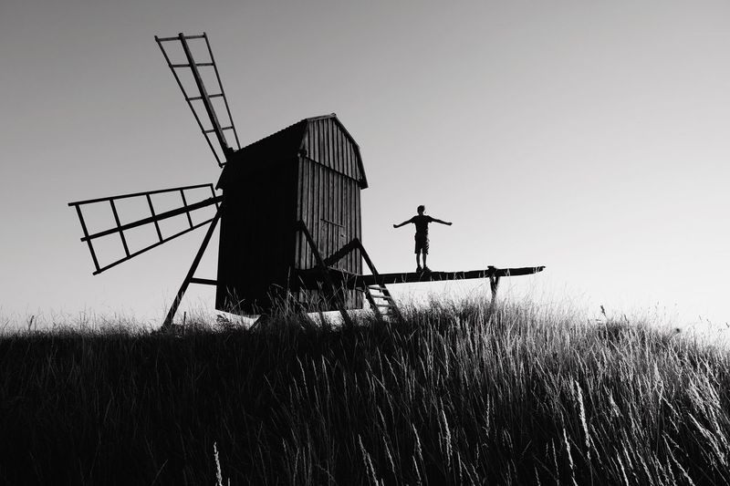 Silhouette traditional windmill on field against clear sky