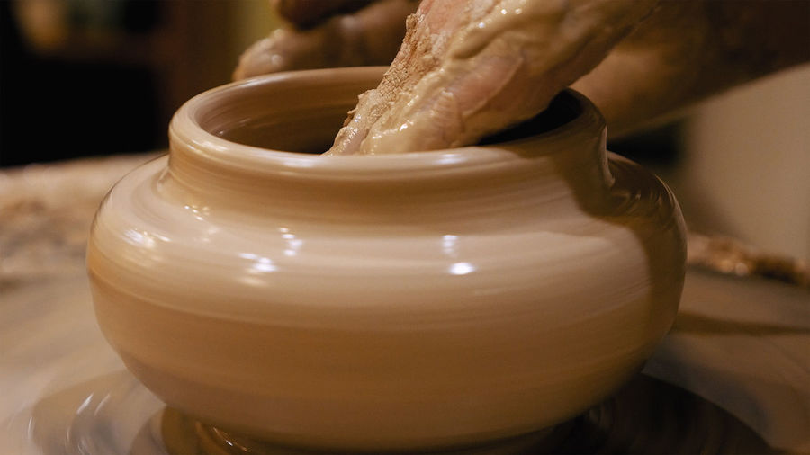 Cropped Hand Shaping Clay Pot