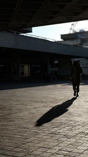 Rear view of silhouette man walking on zebra crossing in city