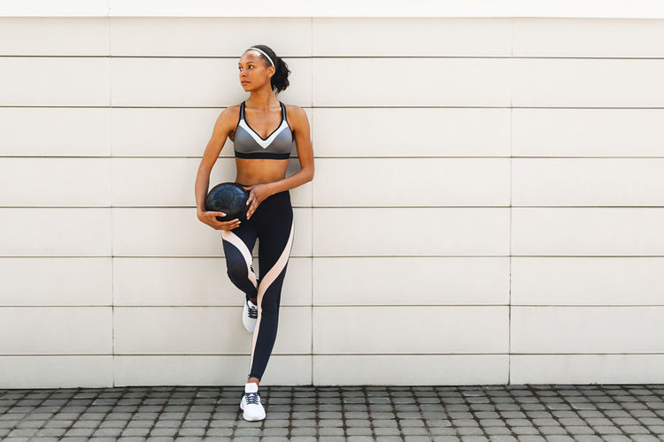 Young Woman In Sports Clothing Holding Ball While Leaning On White Wall
