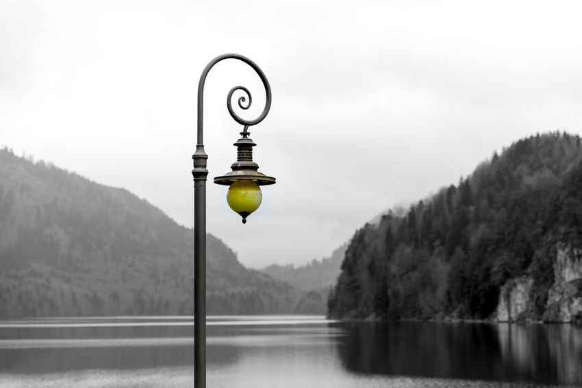 Lone street lamp on the shore of Alpsee. Beauty In Nature Day Lake Mountain Nature No People Outdoors Reflection_collection Scenics Sky Tranquility Tree Water
