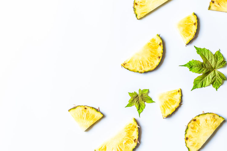 Directly above shot of pineapple slices on white background