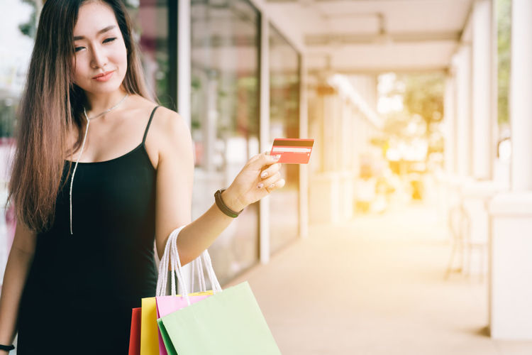 Smiling Young Woman Holding Credit Card And Shopping Bags