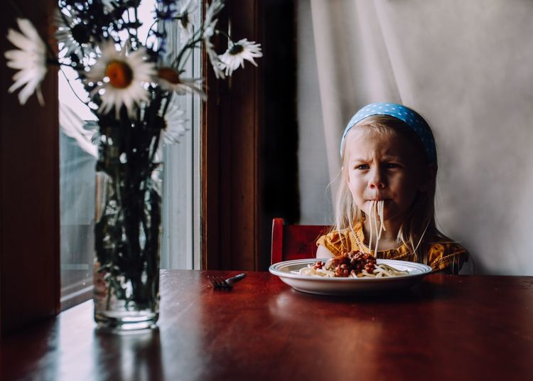 Girl looking away while eating food on table