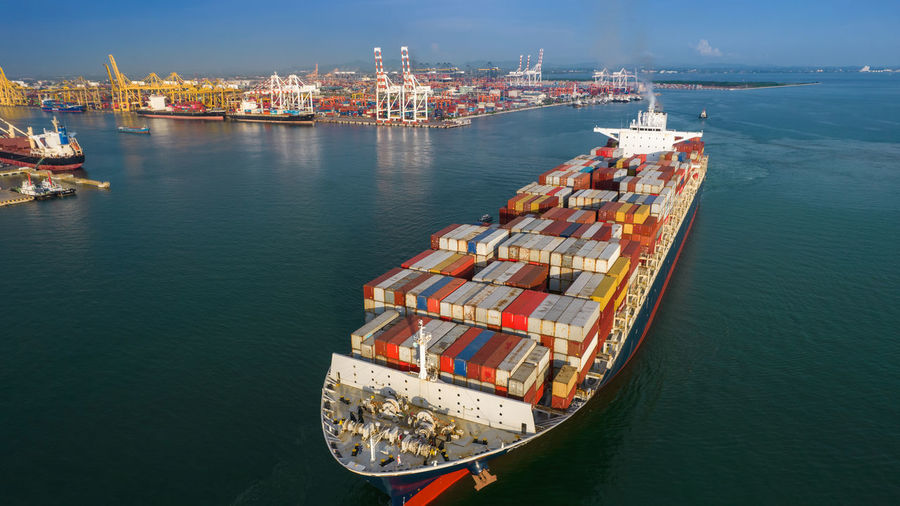 Aerial in front of smart cargo ship carrying container and running