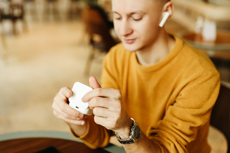 Happy smiling cool young business man freelance student working with wireless technology in a cafe