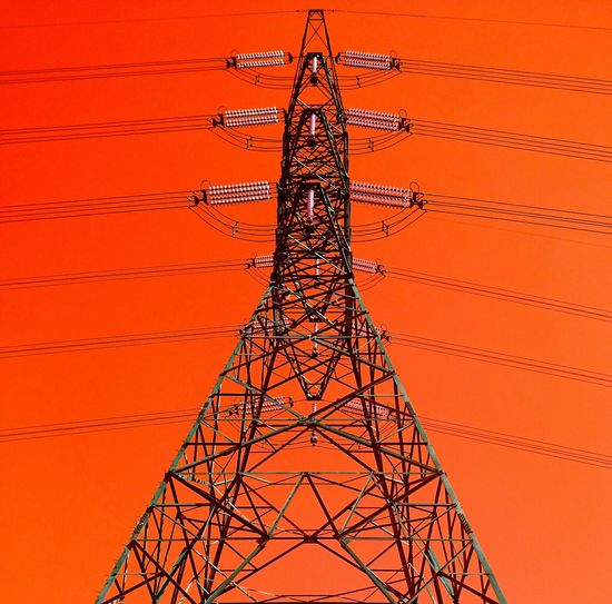 Low Angel View Of Electricity Pylon Against Clear Sky During Sunset