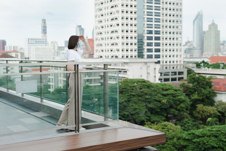 Solo asian woman wear protective mask during outdoor break and relax at rooftop with city background