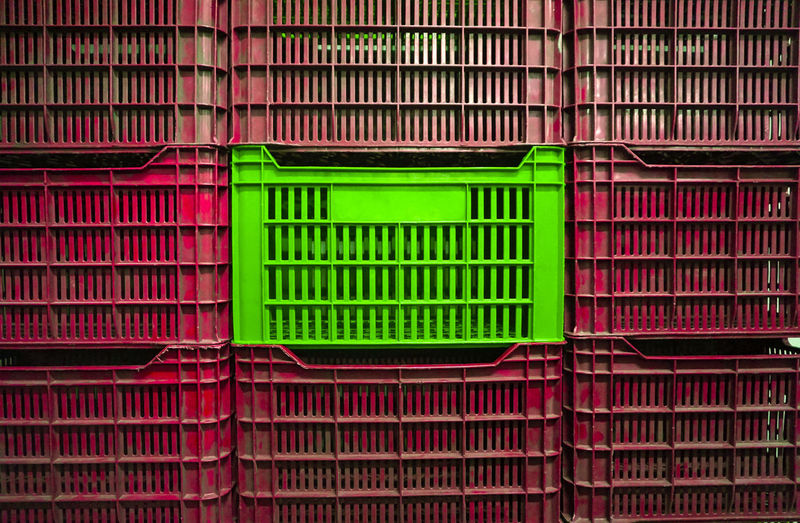 Green safe between plastic red crates.