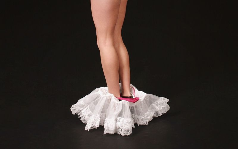 Low Section Of Woman With Tutu On Black Background