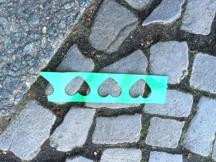 High angle view of heart shape paper on cobbled street