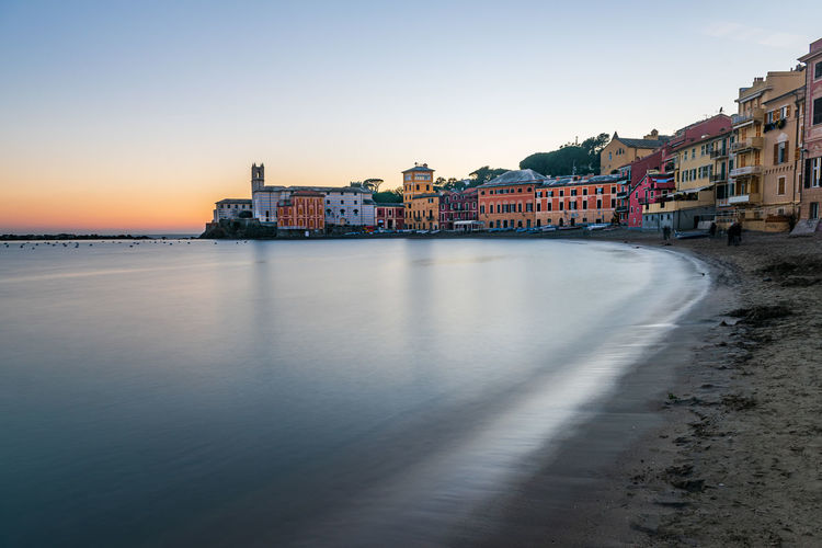 Buildings by sea against clear sky during sunset