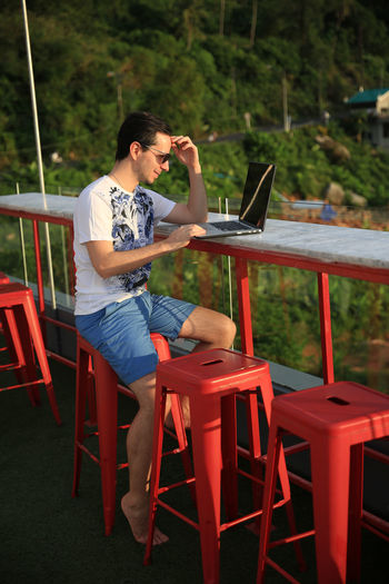 Young man working on computer while on holiday. Freedom Holiday Holidays IT Phuket Working Holiday  Beach Business Man Business Travel Communication Computer Concept Connection Director Distance Work Enterpreneur Internet Laptop Pool Telecommuting Wifi Work And Travel Work From Home