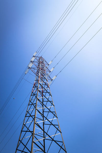 Overhead power line and a pylon against the blue sky Against Blue Cable Cables Current Electric Electrical Electricity  Energy Generation Grid High Industry LINE Lines Mast Overhead Pipeline Power Production Pylon Pylons Sky Structure Supply