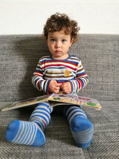 Portrait of cute boy with book sitting on sofa at home