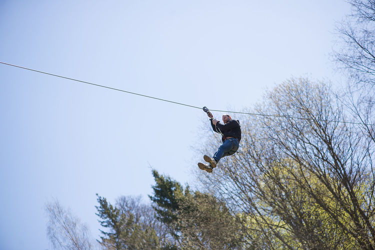 Low Angle View Of Man Zip Lining Against Clear Sky