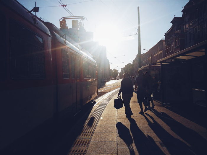 People On Sidewalk By Tram In City